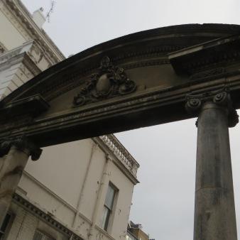 Old gate between modern buildings